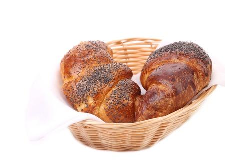 Croissants with poppy on wicker basket.  photo