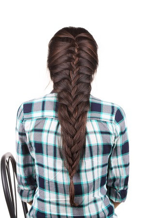 Back side of pretty girl with long braid. Isolated on a white background. Stock Photo