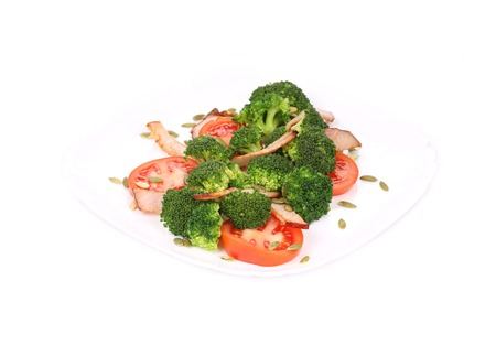 Broccoli salad with ham and pumpkin seeds. Isolated on a white background. photo