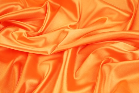 Closeup of elegant shiny orange silk background. Whole background. photo