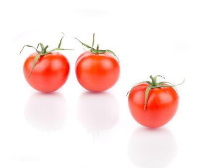 Three fresh ripe tomatoes. Isolated on a white background. photo