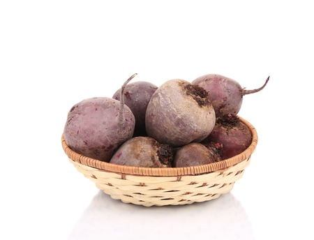 Wicker basket full of ripe beetroots. Isolated on a white background. photo