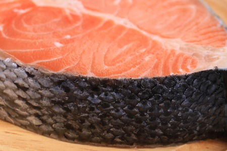 Closeup of beautiful raw salmon steak on cutting board. photo