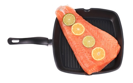 Raw salmon steak on frying pan. Isolated on a white background. photo