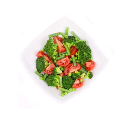 Broccoli salad with french beans and tomatoes. Isolated on a white background. photo