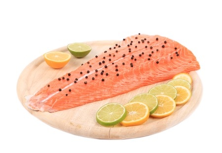 Raw salmon steak on cutting board. Isolated on a white background. photo