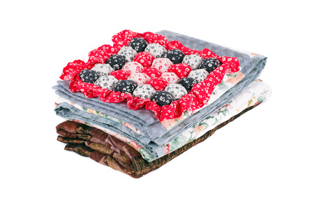 Stack of beautiful handmade quilts. Isolated on a white background. photo