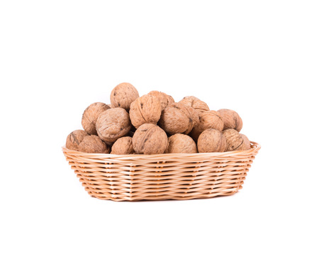 Wicker basket full of walnuts. Isolated on a white background. photo