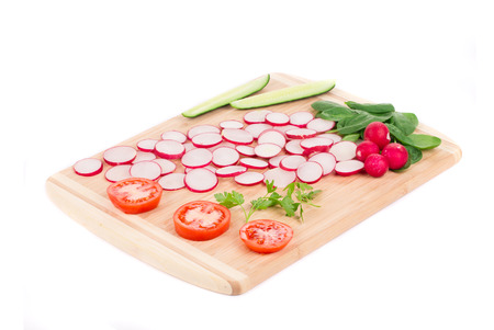 Fresh sliced vegetables on cutting board. Isolated on a white background. photo