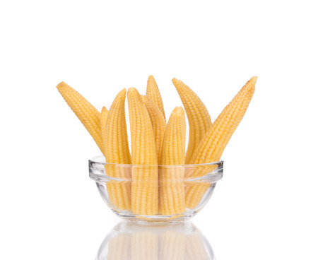 Pickled small corn in glass bowl. Isolated on a white background. photo