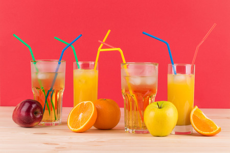 Orange and apple juices on wooden table. On a red background. photo