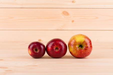 Three fresh red apples on wood background. Whole background. photo