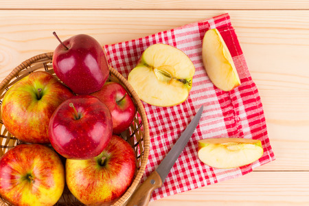 Fresh red apples in basket on wood. Whole background. photo