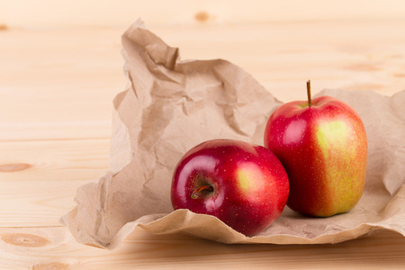 Fresh red apples on paper and wood.  photo