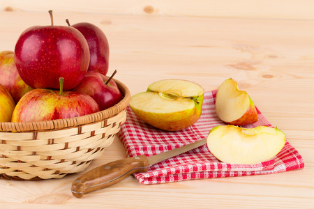 Basket of ripe apples with knife and sliced apple located on wooden table photo