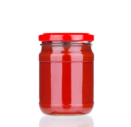Glass jar full of tomato sauce. Isolated on a white background. photo