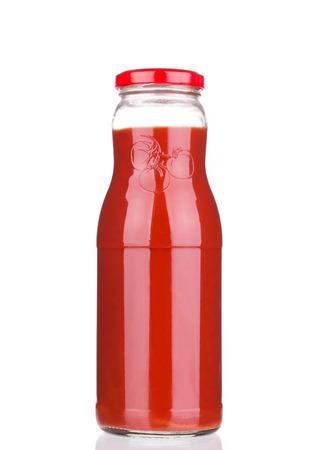 Glass bottle full of tomato juice. Isolated on a white background. photo