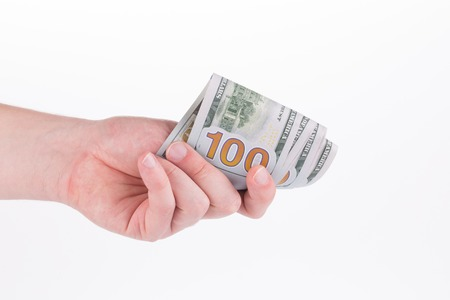 Hand holding hundred dollar bill. Isolated on a white background. Stock Photo
