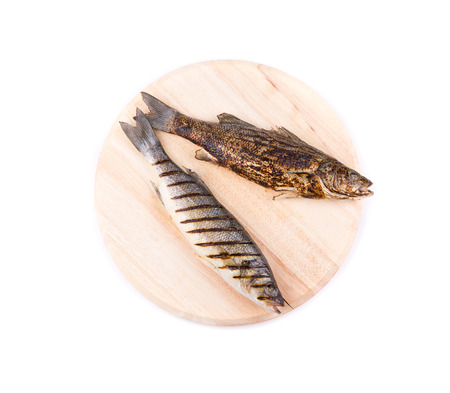 Two grilled seabass fish on platter. Isolated on a white background. photo