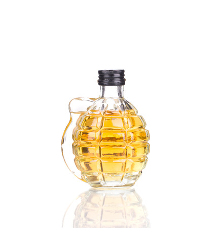Glass in form of grenade full of whiskey. Isolated on a white background.