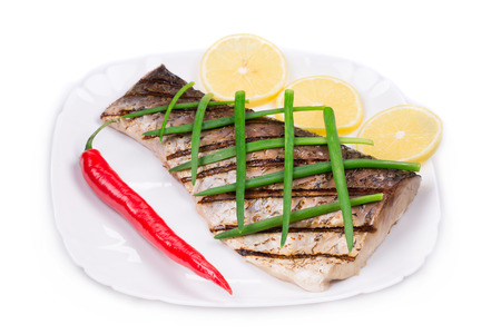 Grilled carp fillet on plate. Isolated on a white background. photo