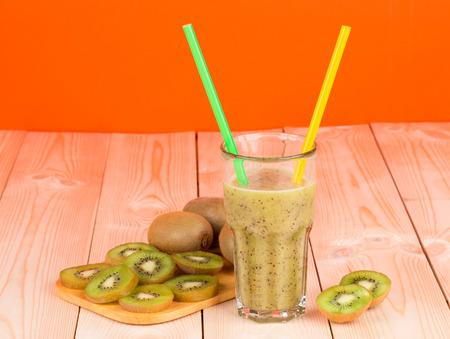 Kiwi juice on the wooden desk and on the orange background photo