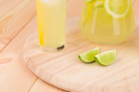 Lime slices with lemonade on the wooden desk photo