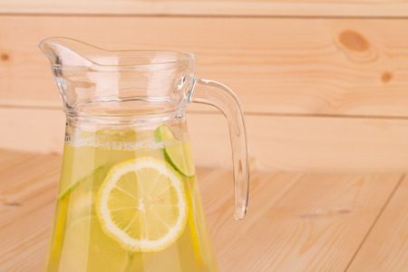 Fresh lemonade on wooden background close up photo