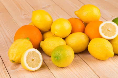 Lemons and oranges on table background closeup