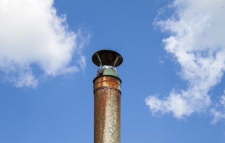 Metal pipe against the sky. Blue sky and white clouds.