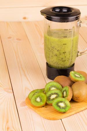 Kiwi juice on the wooden desk closeup photo