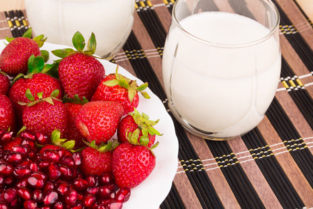 Pomegranate and strawberries with milk. Located on the striped place-mat. photo