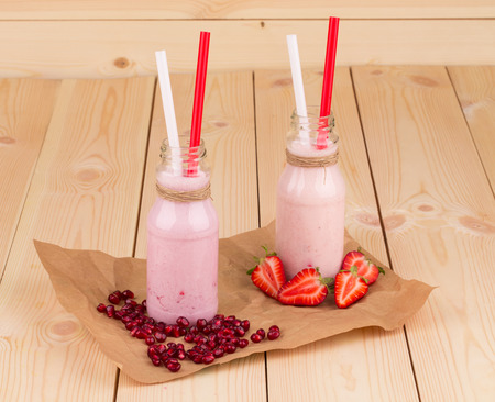 Two berry smoothie present in a little milk bottles photo