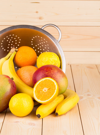 Colorful festive assortment of halved citrus fruit and mangoes arranged on a wooden board photo