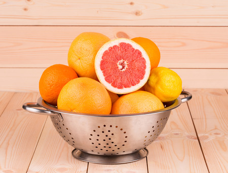 Colorful festive assortment of halved citrus fruits arranged on a wooden board photo