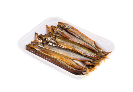 Smoked fishes on a plate. Isolated on a white background. photo
