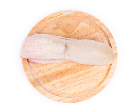 cow tongue: Raw cow tongue on wooden platter. Isolated on a white background.