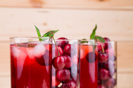 drupe: cherry juice with cherries isolated on a wooden background