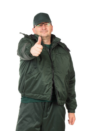 workwear: Worker in winter workwear with thumb up. Isolated on a white background.