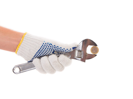 euro screw: Hand in gloves holding adjustable wrench. Isolated on a white background.