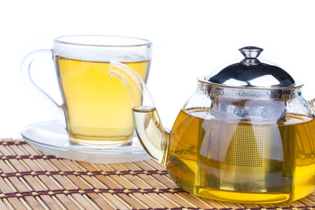 teapot and cup with linden tea on wooden table photo