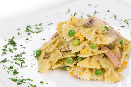 Pasta farfalle with ham and mushrooms. Isolated on a white background. photo
