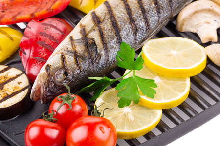 pikeperch: Grilled fish with vegetables. On a black pan.