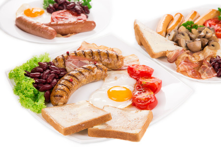haute cuisine: Traditional Full English Breakfast with fried eggs sausages beans mushrooms and bacon as haute cuisine Stock Photo