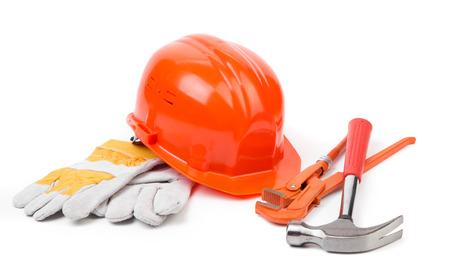 casco rojo: Casco rojo y herramientas de trabajo. Aislado en un fondo blanco.