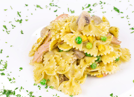 haute cuisine: Pasta farfalle with ham and mushrooms as haute cuisine. Isolated on a white background.