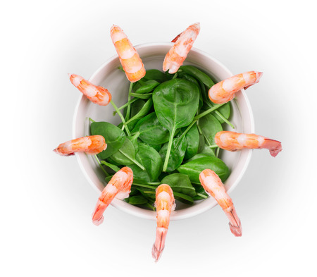haute cuisine: Boiled shrimps and fresh spinach as haute cuisine. Isolated on a white background. Stock Photo