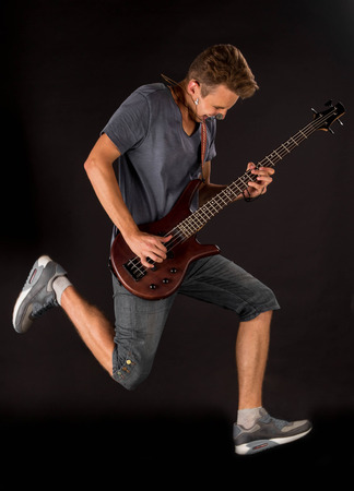 chap: Bass guitarist. Located on the black background. Stock Photo