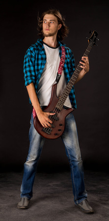 bloke: Bass guitarist. Located on the black background. Stock Photo