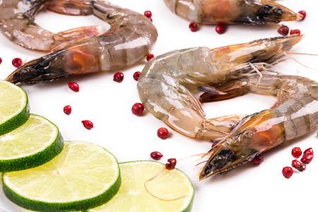 Raw shrimps with lemon. Isolated on a white background. photo